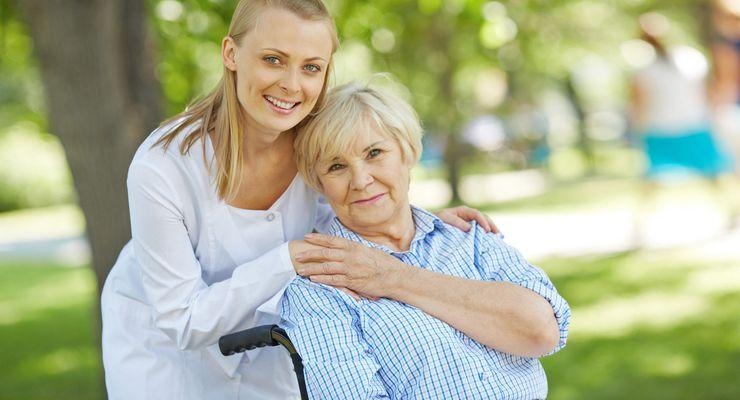 Junge Pflegerin kümmert sich um Patientin im Rollstuhl ml_pflegeheim.jpg