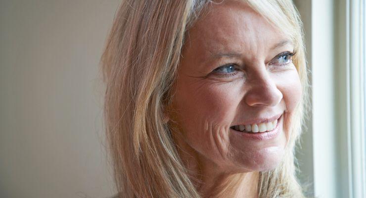 50-jährige Frau schaut lächelnd zum Fenster hinaus mg_wechseljahre_rechts.jpg