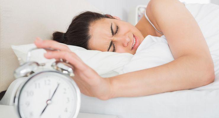 Aufwachende Frau drückt den Wecker aus mg_wecker.jpg