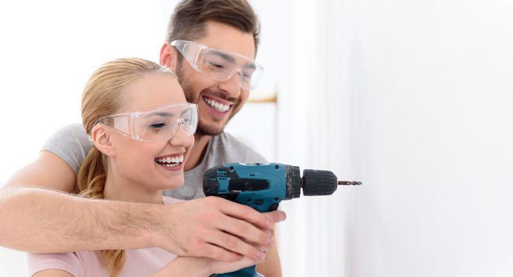 Mann hilft seiner Frau beim Arbeiten mit einer Bohrmaschine mg_heimwerken.jpg