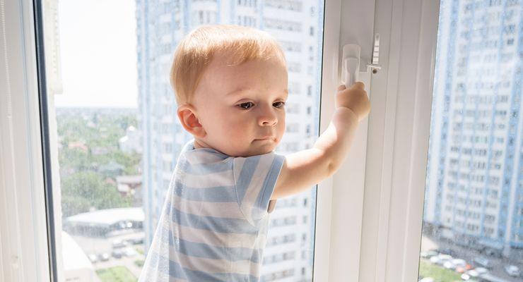Kleiner junge klettert an einem Fenster herum mg_kindersicherheit_zuhause.jpg