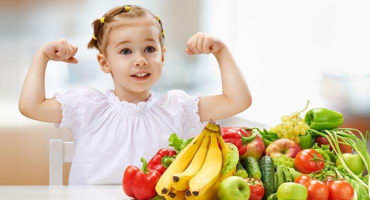 Kind spannt die Arme an und steht vor Obst mg_obst_gemuese.jpg