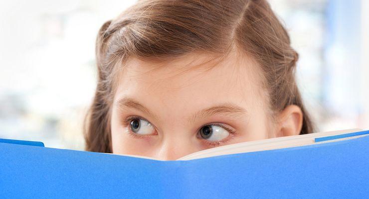 Mädchen schaut über einen Schulheftrand hinweg mg_adhs.jpg