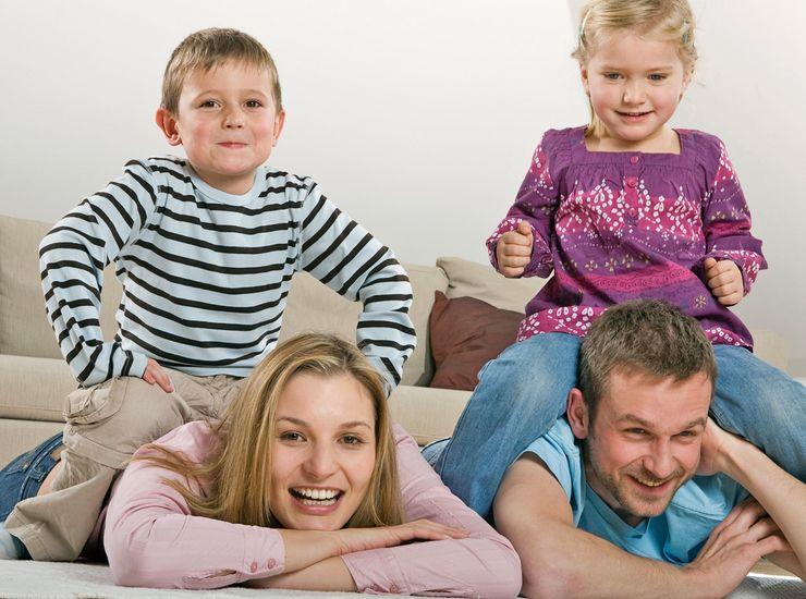 Kinder sitzen auf Ihren Eltern im Wohnzimmer ml_mehrleistungspaket.jpg