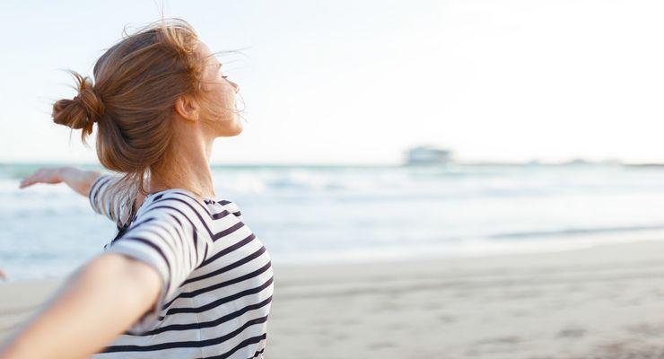 Frau entspannt am Strand mit ausgebreiteten Armen mg_freiheit.jpg