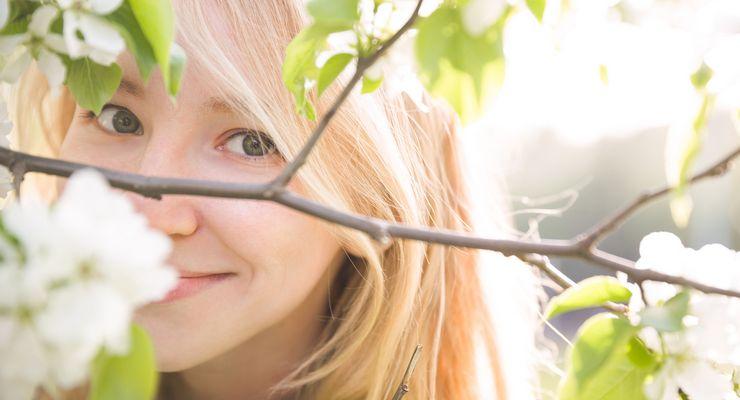 Junge Frau schaut durch die Zweige eines blühenden Baumes mg_fruehling.jpg