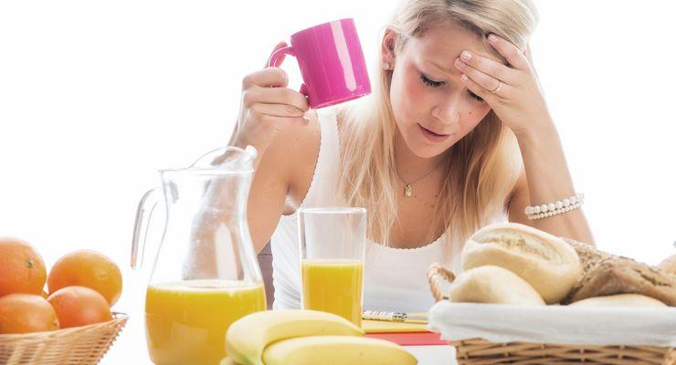 Junge Frau am Frühstückstisch fühlt sich nicht gut mg_lebensmittelunvertraeglichkeit.jpg