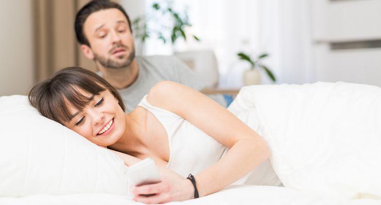 Mann schaut eifersüchtig einer Frau über die Schulter, die gerade etwas auf einem Smartphone liest mg_eifersucht.jpg