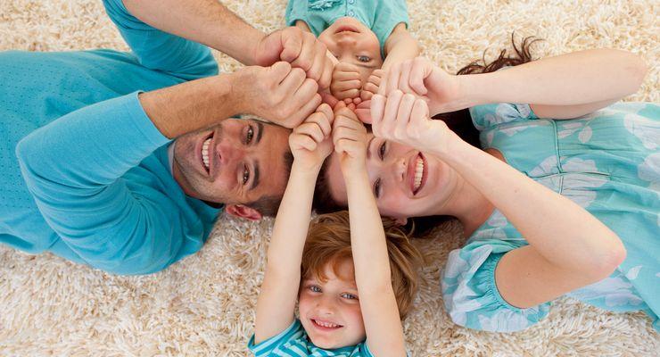 Familien liegt auf den Boden und drückt alle Daumen ms_zusatzversicherungen.jpg