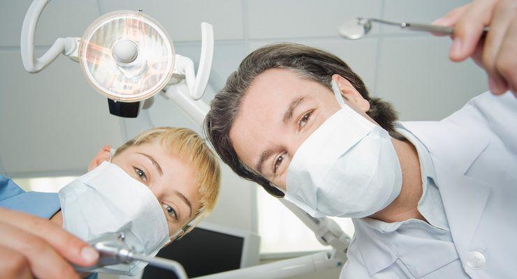 Zahnarzt und Zahnarzthelferin schauen in die Kamera ml_zahnaerztliche_behandlung.jpg