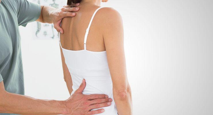 Physiotherapeut untersucht eine junge Frau mg_rueckenhaltung1.jpg