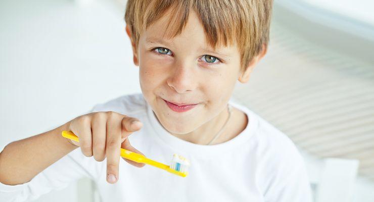 Junge mit einer Zahnbürste in der Hand zeigt in die Kamera mg_zanhpflege_kinder.jpg