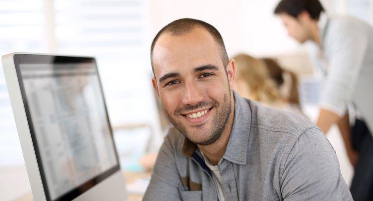 Mitarbeiter vor Computer lächelt in die Kamera mg_bueroluft.jpg