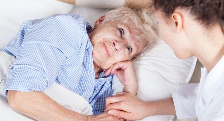 Ältere Frau im Bett wird von junger Pflegerin versorgt ml_pflegehilfsmittel.jpg