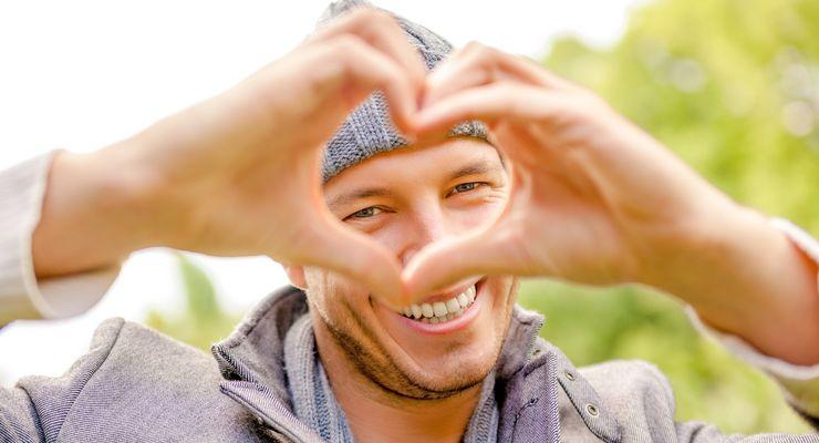 Ein lächelnder junger Mann zeigt mit seinen Händen eine Herzform mg_gute-laune-herbst.jpg