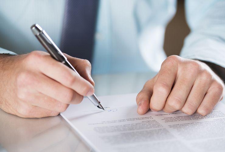 Mann unterschreibt ein Schriftstück ueu_satzung.jpg
