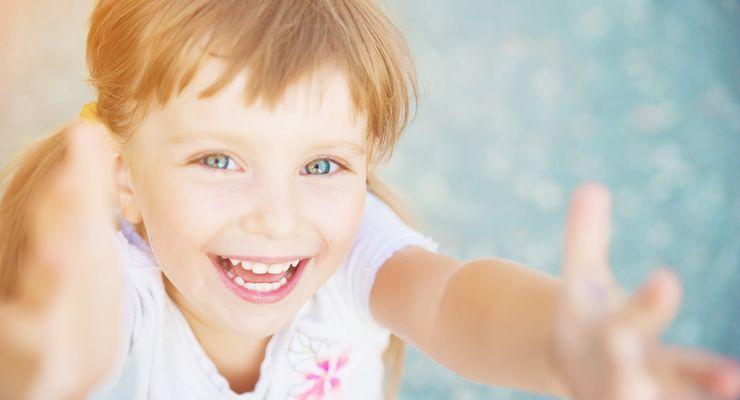 Kleinkind schaut lachend nach oben in die Kamera ml_augenscreening.jpg