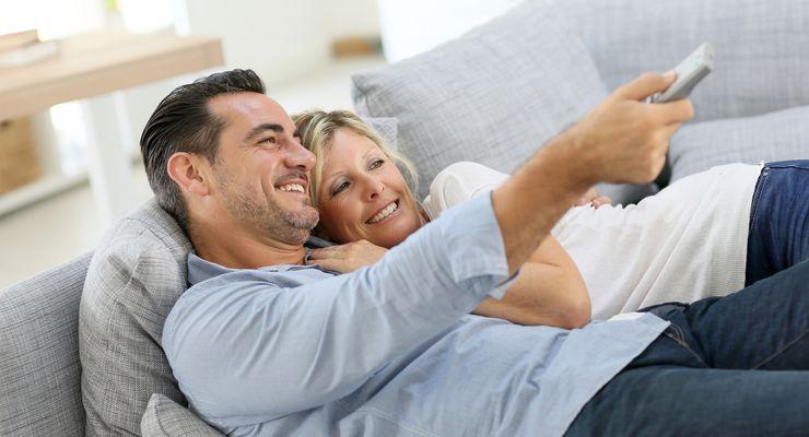 Ein Paar liegt auf der Couch und sieht gemeinsam fern mg_couchpotatoes.jpg