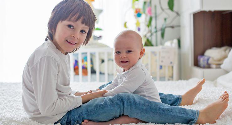 Schulkind und Baby sitzen auf einem Bett mg_kinderbetten.jpg