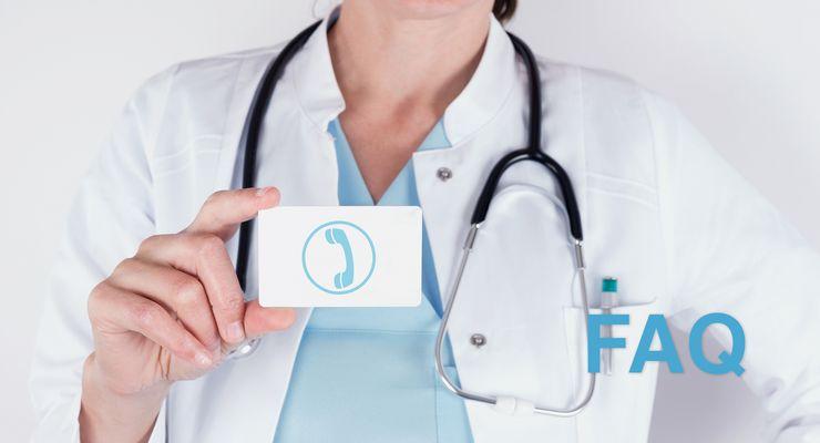 Ärztin hält eine kleine Tafel mit einem aufgedruckten Telefonsymbol in der Hand ms_corona_faq.jpg
