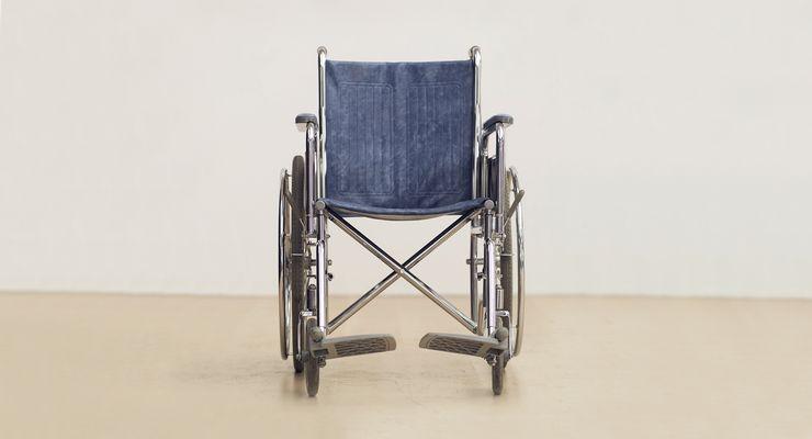 ein leerer Rollstuhl vor eine weißen Wand ml_hilfsmittel.jpg